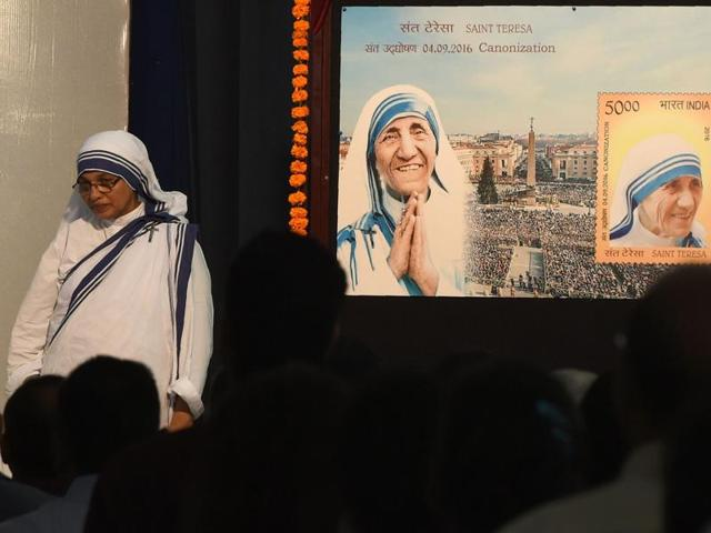 A Christian Nun stands next to a board displaying a commemorative postage stamp of Mother Teresa during its release function in Mumbai on September 4.