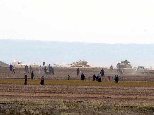 Syrian civilians, with Turkish Army tanks in the background, walk through the Turkish border as they are pictured from a village in Kilis province.