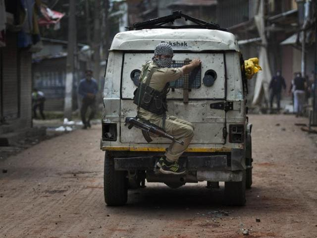 A police officer takes cover behind an armoured vehicle as Kashmiri protesters throw stones at him during a protest in Srinagar on August 30.