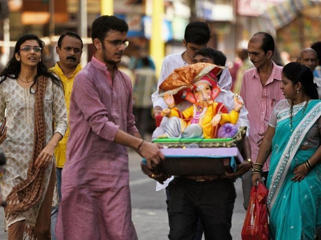 Family's take home Ganesha idols in Girgaum on Monday.