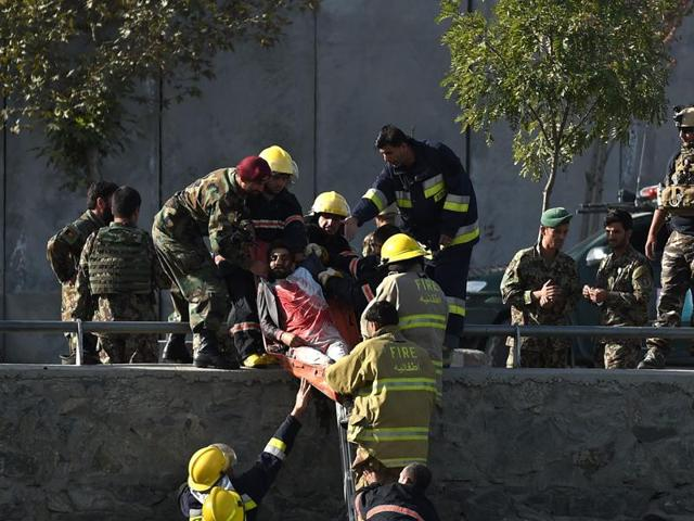 Afghan security personnel and firemen recover a body from the scene of a twin suicide bombing near the Ministry of Defense in Kabul.