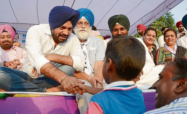 Comedian and newly appointed Punjab convener of AAP Gurpreet Ghuggi shaking hands with a child during a rally in Amritsar on Sunday.