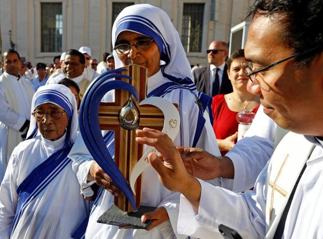 Indian Christians and nuns gathered to pay their respects by a portrait of Mother Teresa in Siliguri before her canonisation.