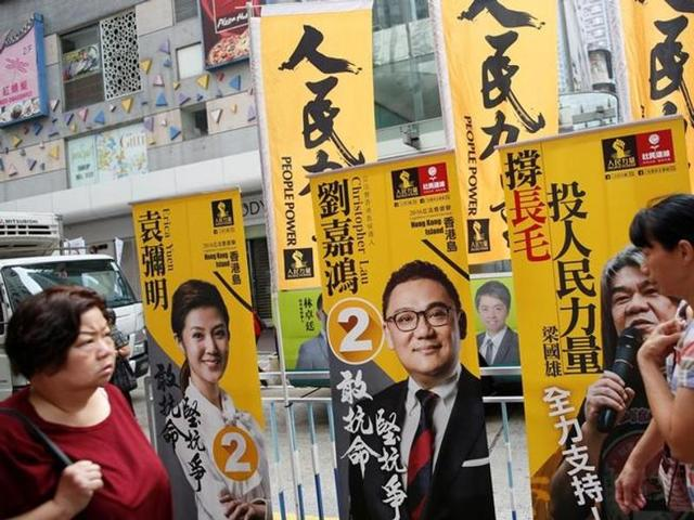 People walk past banners candidates on election day for Hong Kong's legislative council.