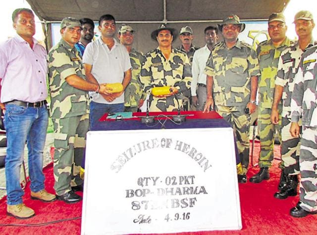 BSF officials with seized heroin at Indo-Pak border in Ferozepur on Sunday.