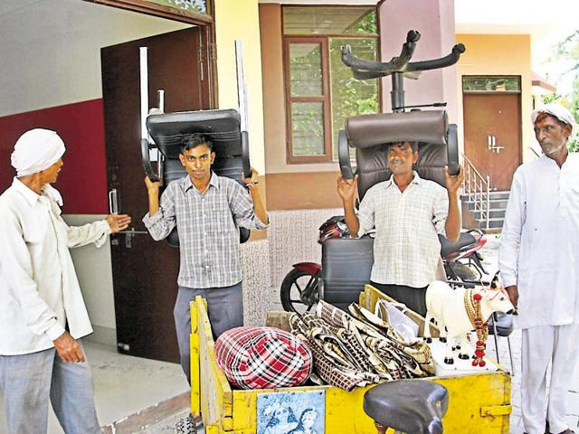 Workers shifting Haryana minister Manish Grover's furniture into an MC building in Rohtak on Sunday.
