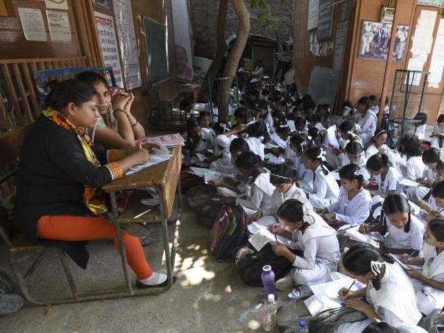 Teachers conduct classes outdoors at a government school in Mustafabad, Delhi.