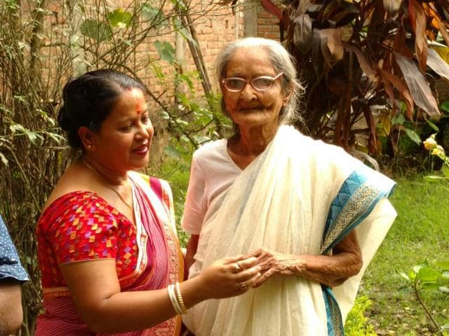 Aruna Mukherjee (R)  who was born in Dhaka, Bangladesh and came to Assam 80 years ago after her marriage is seen here with her aide Ganga (L).