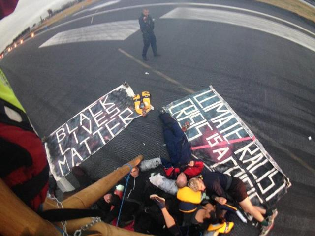 Emergency services surround protestors from the movement Black Lives Matter after they locked themselves to a tripod on the runway at London City Airport in London.
