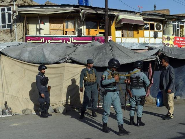 Afghan security personnel and firemen recover a body from the scene of a twin suicide bombing near the Ministry of Defence in Kabul on September 5, 2016.