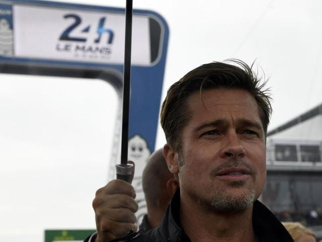Brad Pitt removes his helmet after a full lap on the Le Mans 24 Hours circuit.