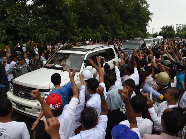 Demonstrators chant 'Kofi Annan go away' while a police car escorts the vehicle carrying the former UN secretary general in Sittwe.
