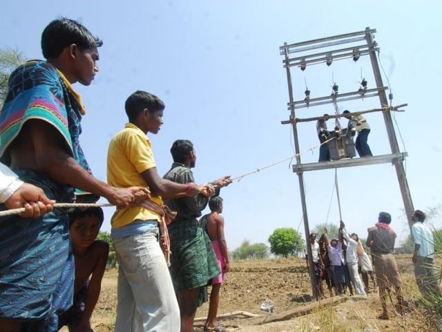 Villagers of Kenda Bahali are waiting and helping worker of the Electrification Scheme.
