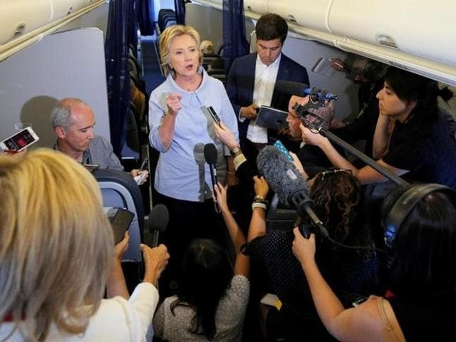 US Democratic presidential candidate Hillary Clinton answers questions from reporters on her campaign plane enroute to a stop in Moline, Illinois.
