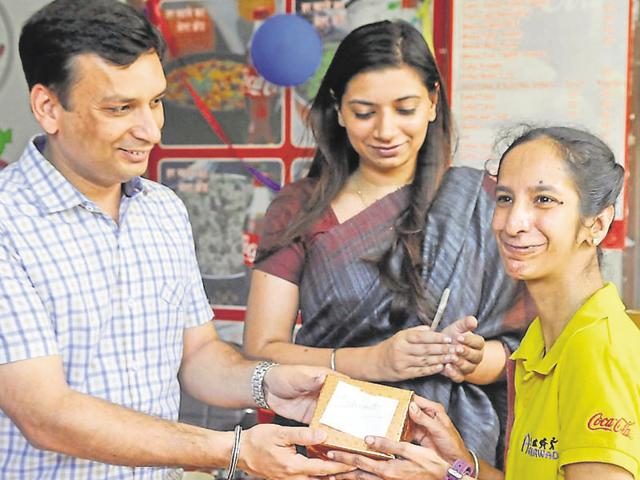 Ludhiana DC Ravi Bhagat giving a gift to a special child who runs the canteen in city on Monday.
