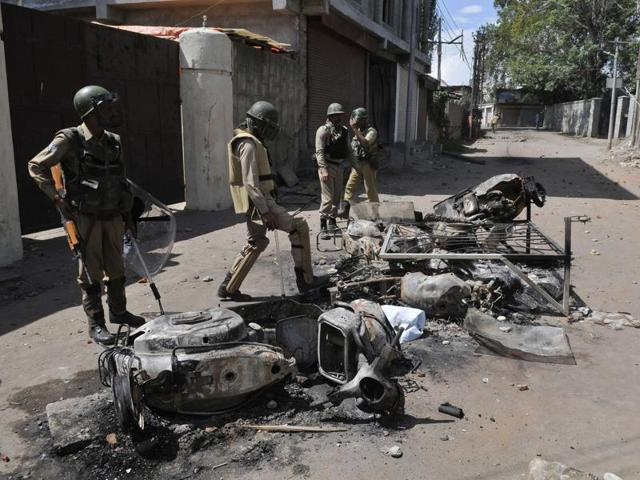 Paramilatary soldiers stand near burnt vehicles which were set on fire by protesters during clashes in Srinagar.
