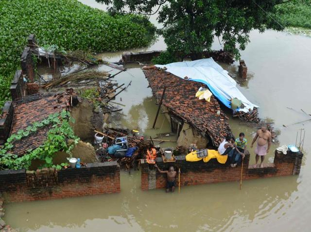 A family sit at their destroyed house amidst the floodwaters after heavy rains in Gaya.