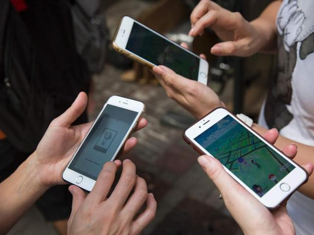 Participants use their smartphones as they play the gaming app Pokemon Go during a 'PokeWalk' in Hong Kong.