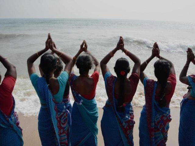 Women offer prayers during a ceremony for the victims of the 2004 earthquake and tsunami at Marina Beach in Chennai.