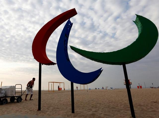 Men push a cart on the sand next to the Paralympic symbol.