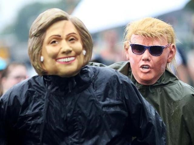 Protesters wearing masks of presidential candidates Hillary Clinton and Donald Trump
