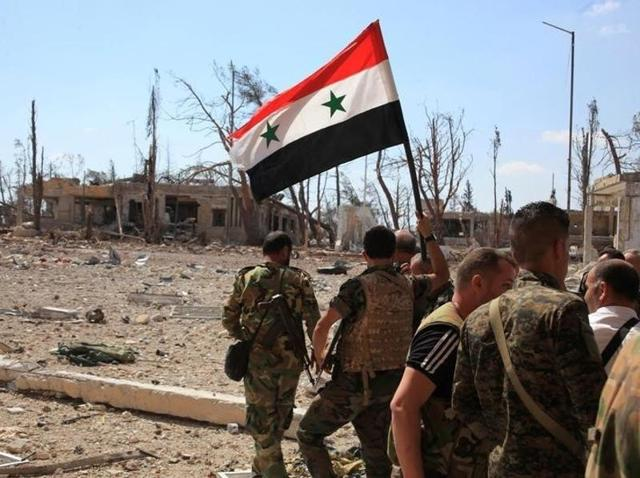 Forces loyal to Syria's President Bashar al-Assad walk at a military complex as one of them holds up a Syrian national flag, in Aleppo.