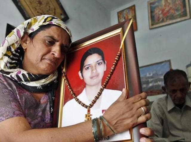 Roshni Rathi holds a photograph of her daughter Preeti-at their Narela residence.