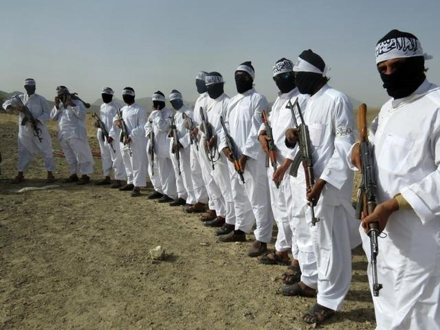 In this August 15, 2016 photo, Taliban suicide bombers stand guard during a gathering of a breakaway Taliban faction, in the border area of Zabul province, Afghanistan.