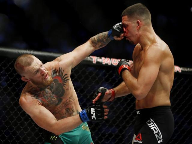 Nate Diaz, right, punches Conor McGregor during their welterweight mixed martial arts bout at UFC 202.
