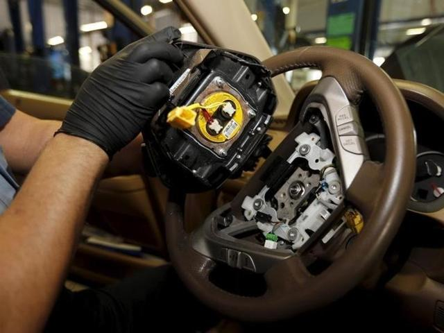 A recalled Takata airbag inflator is held after it was taken out from a Honda Pilot at a Honda dealership.