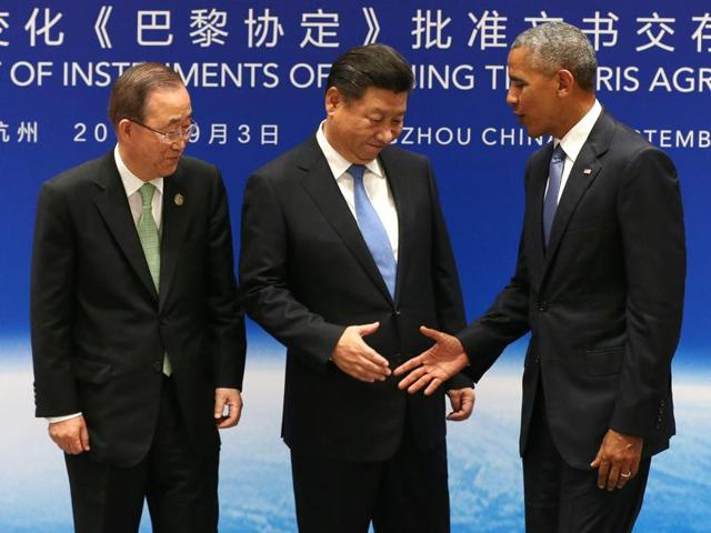 Chinese president Xi Jinping shakes hands with US president Barack Obama as UN secretary general Ban Ki-moon looks on during a joint ratification of the Paris climate change agreement ahead of the G20 Summit in Hangzhou on September 3, 2016.