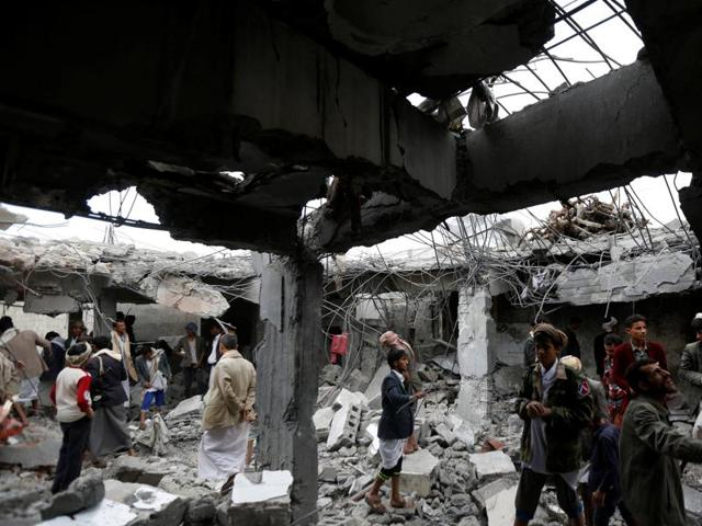 People gather at a building destroyed by Saudi-led air strikes in the northwestern city of Amran, Yemen September 8, 2016.