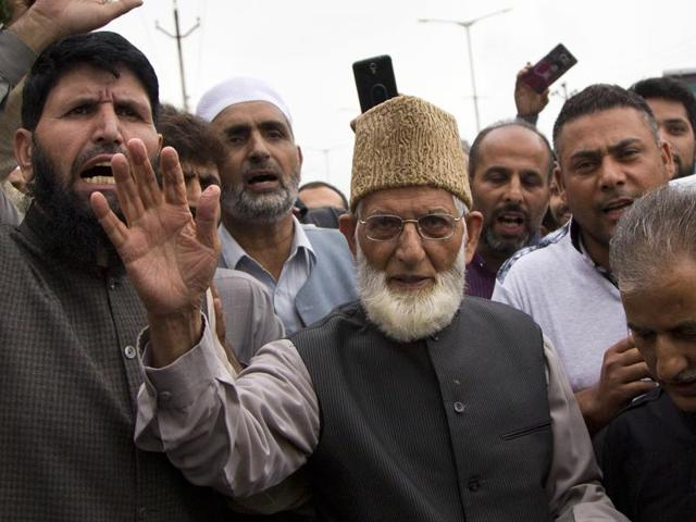 Separatist leader of the hardliner faction of All Parties Hurriyat Conference Syed Ali Shah Geelani waves to his supporters outside his house as he arrives to participate in a march towards an army base in Srinagar.
