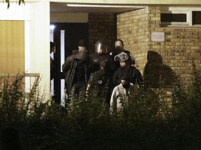 A handcuffed man is taken out of the building in Boussy-Saint-Antoine south of Paris on September 8, 2016 where female suspects, said to have been planning new acts of violence, were arrested.
