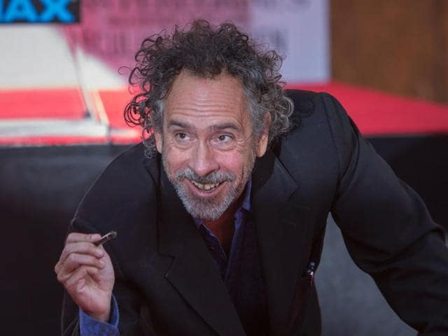 Film director Tim Burton looks up as his signs his name in the cement of the forecourt of the TCL Chinese Theatre on September 8, 2016 in the Hollywood, California.