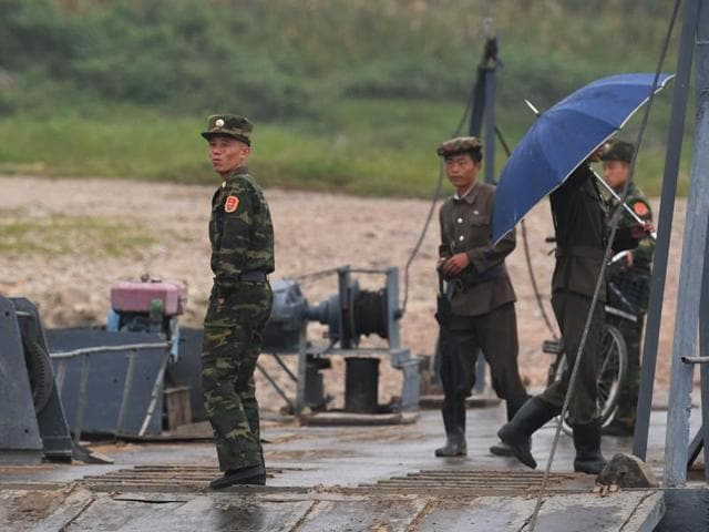 North Korean men stand on a floating jetty on the bank of the Yalu river near Sinuiju, opposite the Chinese border city of Dandong. North Korea said on September 10 it would not submit to US nuclear