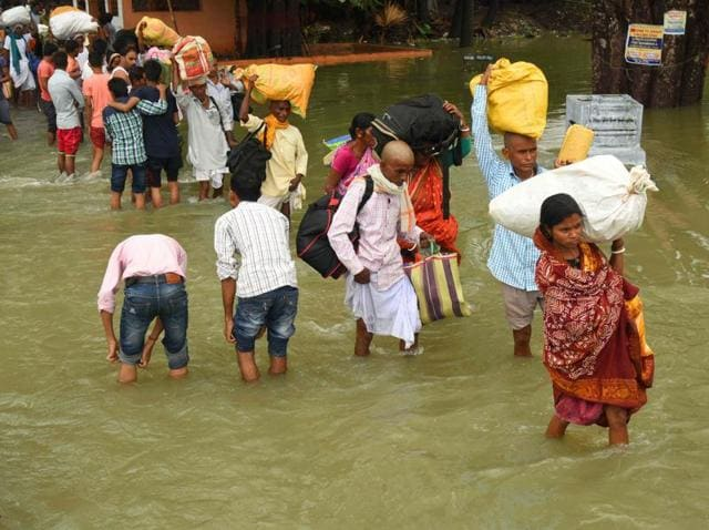 People carry their belongings as they walk through the flooded Pant Nagar area of Gaya.