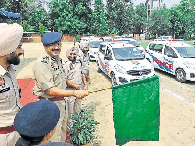 A police officer flagging-off the new fleet of vehicles in Jalandhar on Friday.