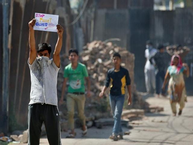 A demonstrator holds a placard during a protest against the recent deaths in Kashmir, Srinagar.