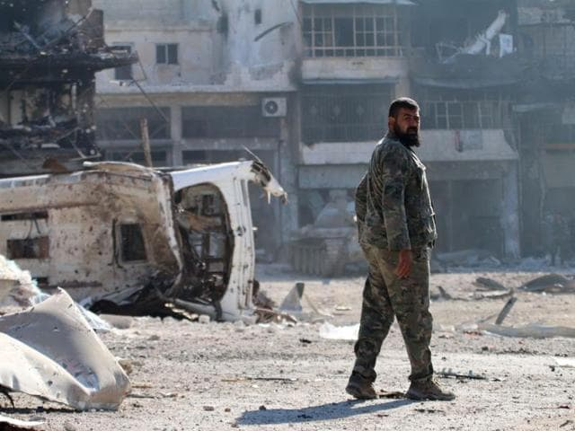 A Syrian pro-regime fighter walks in a bombed-out steet in Ramussa on September 9, 2016, after fellow fighters took control of the strategically important district on the outskirts of the Syrian city of Aleppo the previous day.