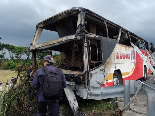 Investigators inspect a bus carrying tourists from mainland China that crashed and caught fire along an expressway on its way to the airport in Taiwan's city of Taoyuan on July 19, 2016.