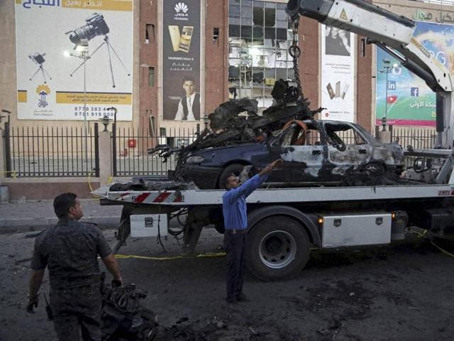 Iraqi security forces clean up the site in the aftermath of car explosion in Baghdad.