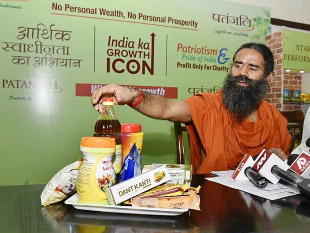 Yoga guru Ramdev displays his company Patanjali's products at a press conference in Delhi.