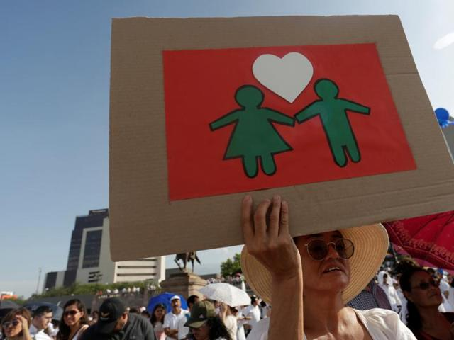 A woman holds a cardboard sign as thousands of Catholics and conservatives gather against the legalization of gay marriage and to defend their interpretation of traditional family values in Monterrey City, Mexico.