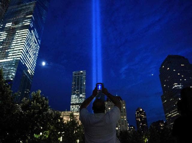 A man photographs beams of light symbolising the two World Trade Center towers the night before the 15th anniversary of the September 11, 2011 terrorist attacks in New York.