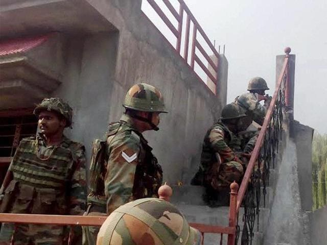 Security personnel take positions near a building where terrorists were holed up during an encounter in Poonch on Sunday.