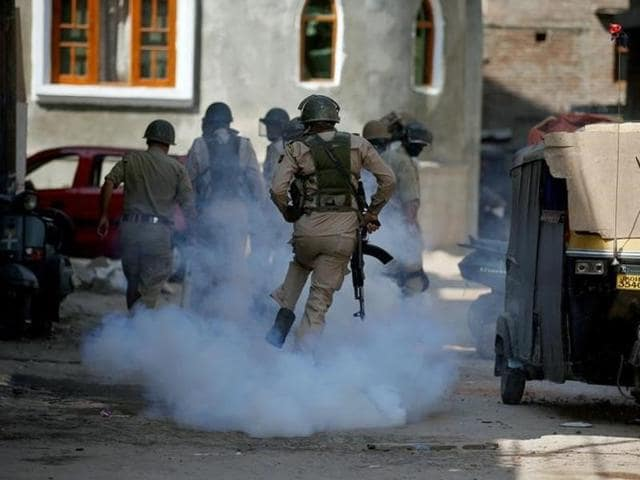 File photo of a  policeman running amid tear gas smoke during a protest  in Srinagar, J-K.  Acivilian was killed in when militants hurled a grenade in the state's Anantnag on Sep 12, 2016,