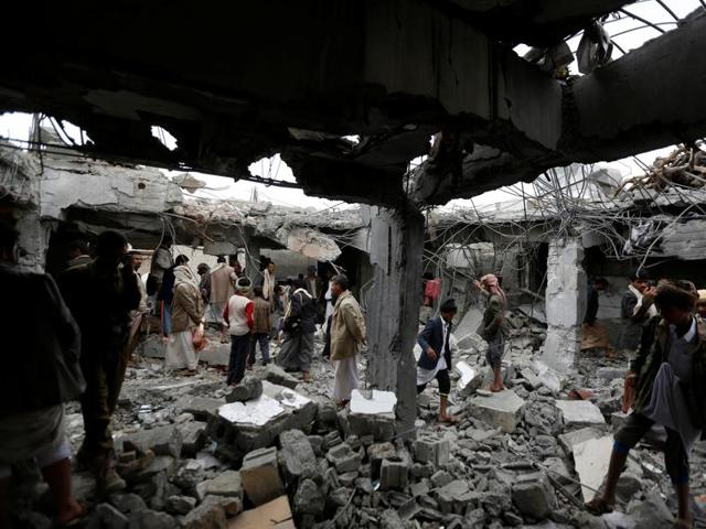People gather at a building destroyed by Saudi-led air strikes in the northwestern city of Amran, Yemen.
