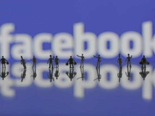 3D-printed models of people are seen in front of a Facebook logo in this photo illustration taken June 9, 2016.