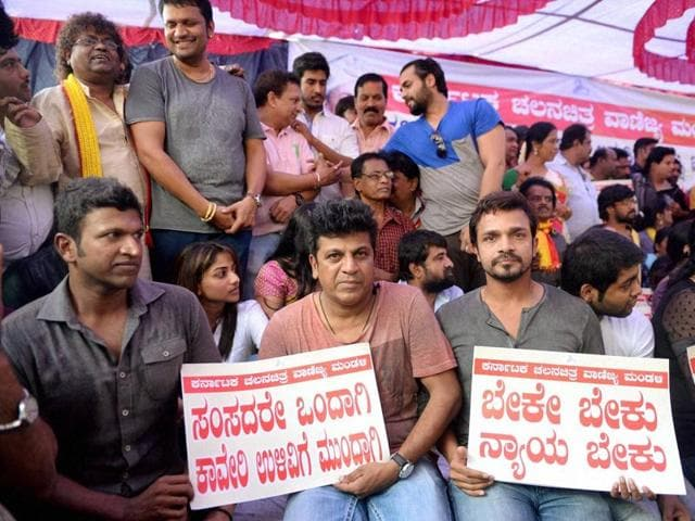 Kannada actors sit on a dharna during Karnataka Bandh called in protest against the Supreme Court verdict on Cauvery water issue, in Bengaluru on Friday.